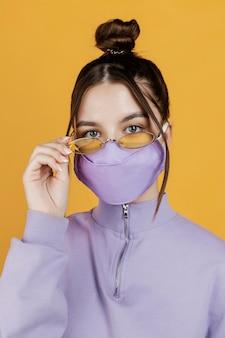 Porträt junge frau, die sonnenbrille und maske trägt