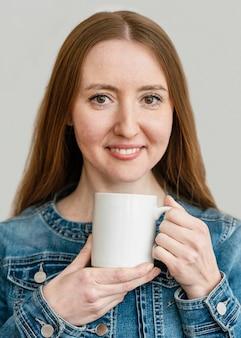 Porträt junge frau, die tasse hält Kostenlose Fotos