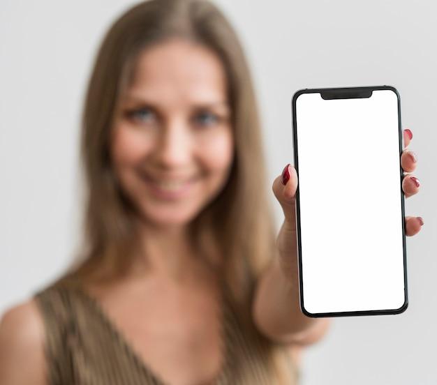 Porträt junge frau, die telefon hält Kostenlose Fotos