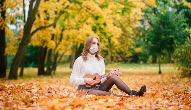 Porträt junge frau in der schutzmaske, die ukulele-gitarre im herbstpark spielt