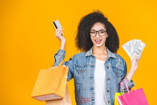 Porträt junge frau lächelnd und freudig mit bunten einkaufstüten, kreditkarte und banknoten lokalisiert über gelbem hintergrund.