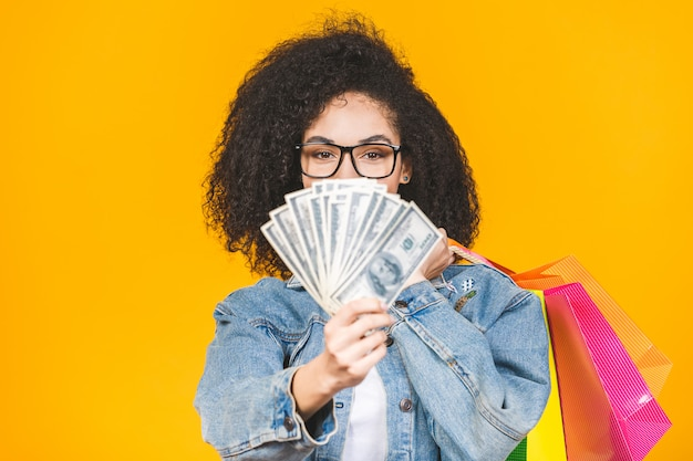 Porträt junge frau lächelnd und freudig mit bunten einkaufstüten und banknoten lokalisiert über gelbem hintergrund.