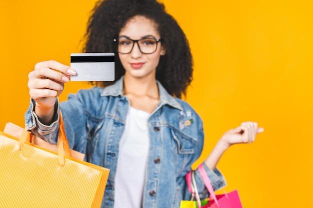 Porträt junge frau lächelnd und freudig mit bunten einkaufstüten und kreditkarte lokalisiert über gelbem hintergrund.