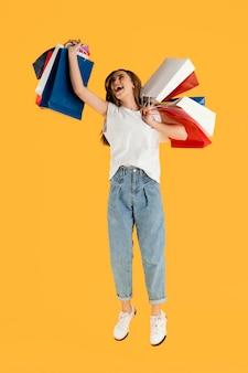 Porträt junge frau mit einkaufstaschen springen