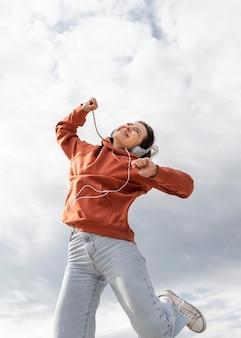 Porträt junge frau mit kopfhörern springen