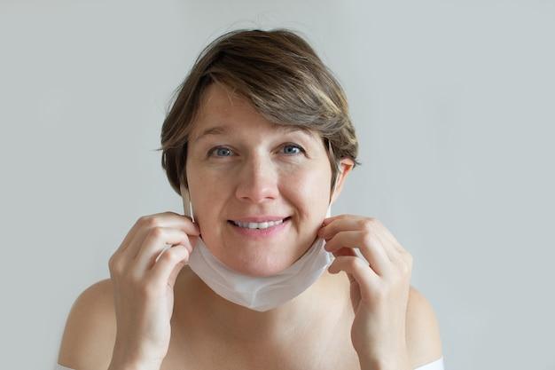 Porträt junge fröhliche frau, die ihre baumwoll-leinenmaske abnimmt.