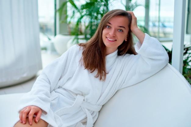 Porträt junge glückliche freudige schöne schöne brünette frau, die weißen bademantel genießt, die entspannende zeit genießt und sich in einem wellness-spa-resort gut fühlt.