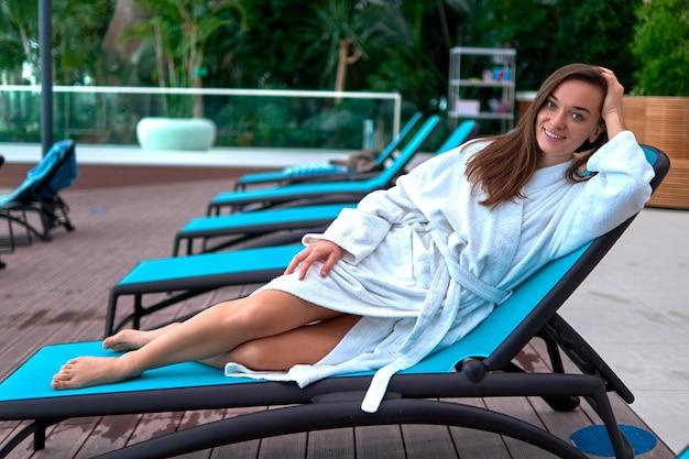 Porträt junge glückliche schöne brünette frau, die weißen bademantel trägt, der auf einer liege am pool liegt und entspannende zeit genießt und sich in einem wellness-spa-resort gut fühlt. einfacher lebensstil