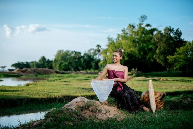 Porträt junge hübsche asiatische frau in schöner thailändischer traditioneller kleidung am reisfeld, sie sitzt in der nähe von angelausrüstung