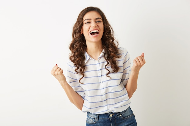 Porträt junge hübsche frau, die mit emotionalem gesichtsausdruck lacht, hände hochhält, erfolg, gewinner, gekleidet in hemd isoliert, glücklich, positive stimmung, aufrichtiges lächeln, langes lockiges haar, weiße zähne
