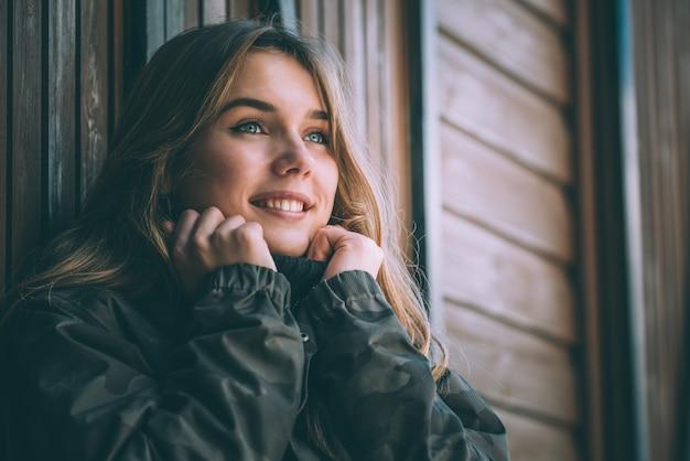 Porträt junge hübsche frau im winter in einem blockhaus im schnee