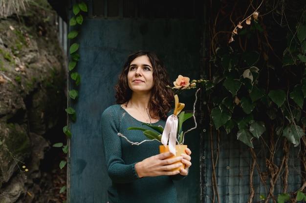 Porträt junge kaukasische frau, die gelbe orchideenpflanze auf einem wilden grünen hintergrund hält.