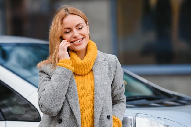 Porträt junge mode schöne frau in der nähe ihres autos, in der stadt. einkaufendes mädchen.