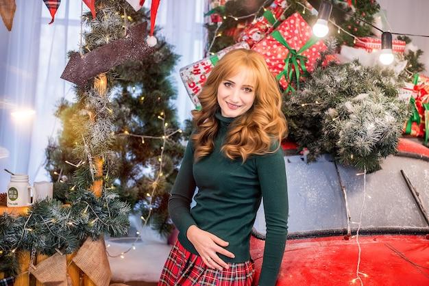 Porträt junge schöne frau nahe dem roten auto, verziert mit weihnachtsbäumen und girlanden mit lichtern, flaggengeschenken.