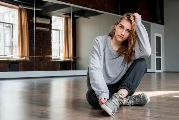 Porträt jungen blondine, die auf dem massivholzboden betrachtet kamera sitzen