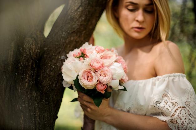 Porträt jungen blondine mit einem blumenstrauß von den blumen, die nahe dem baum stehen