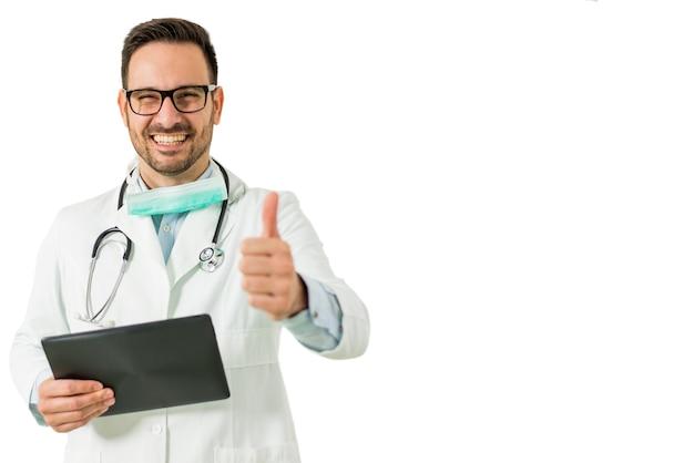 Porträt jungen männlichen doktors mit dem daumen, der oben die digitale tablette lokalisiert auf dem weiß hält