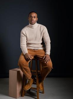 Porträt junger afrikanischer mann, der auf stuhl sitzt