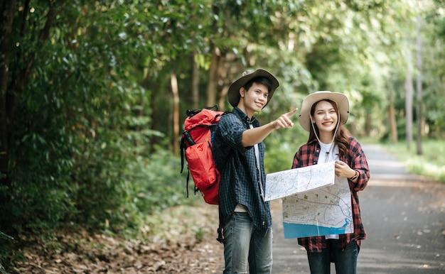 Porträt junger asiatischer gutaussehender mann mit rucksack und trekking-hut und hübscher freundin, die auf der papierkarte steht und die richtung überprüft, während sie auf dem waldweg geht, rucksackreisekonzept