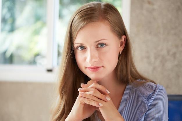 Porträt junger attraktiver dame, die kamera mit ihren händen zusammengepreßt betrachtet