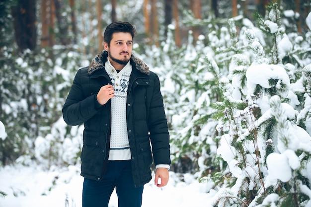 Porträt junger bärtiger männer im wald im winter, daunenjacke
