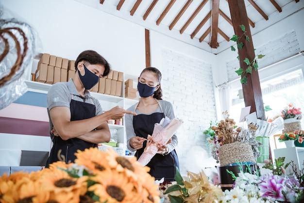 Porträt junger florist stehend, der frische blumen mit freund im blumenladen nach protokoll gesund bespricht