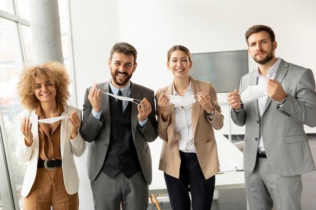 Porträt junger geschäftsleute, die im büro ihre schützenden gesichtsmasken abnehmen