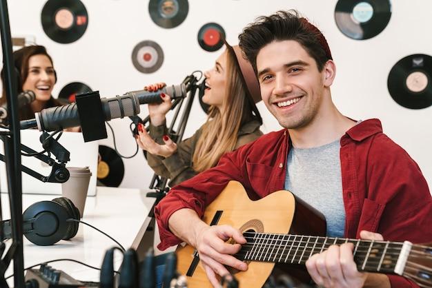 Porträt junger glücklicher kaukasischer menschen, die im radioprogramm auftreten, während sie podcast-aufnahmen für online-shows machen