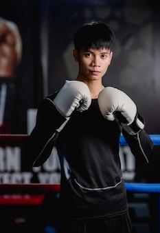 Porträt junger gutaussehender mann in sportkleidung und weißen boxhandschuhen, die auf leinwand im fitness-studio stehen, gesunde mann-trainings-boxklasse,