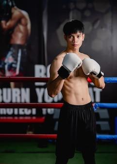Porträt junger gutaussehender mann in weißen boxhandschuhen stehend pose auf leinwand im fitness-studio, gesunder mann training boxklasse,