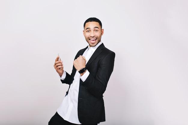 Porträt junger hübscher mann im weißen hemd, schwarze jacke, die spaß hat, lächelnd. erfolg, wahre positive emotionen ausdrücken, gute ergebnisse, glück, lächeln.