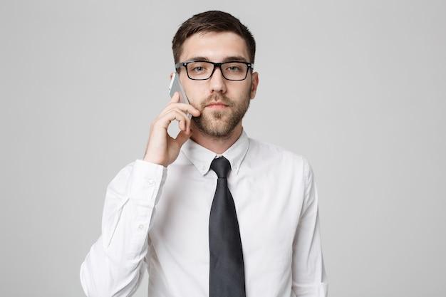 Porträt junger hübscher verärgerter geschäftsmann im anzug, der am telefon spricht, das kamera betrachtet.