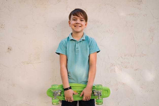 Porträt junger kühler lächelnder junge im blauen polo, der mit penny board in den händen aufwirft