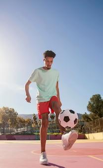 Porträt junger mann, der fußball spielt