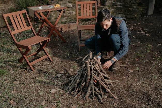 Porträt junger mann, der holzhaufen vorbereitet, um feuer anzuschalten. camping, natürliches lifestyle-konzept.