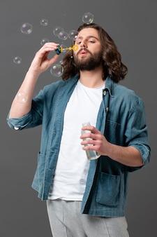 Porträt junger mann, der seifenblase macht
