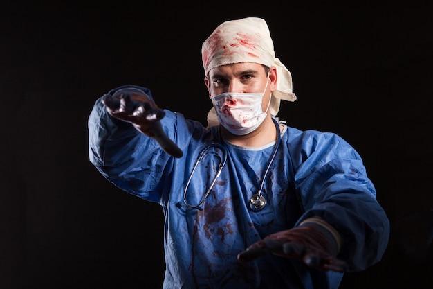 Porträt junger mann in verrückter arztkleidung, die mit seinen händen über schwarzem hintergrund für halloween-karneval ausstreckt. frustrierter arzt mit finsterem blick.
