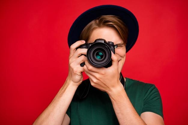 Porträt junger mann mit hut, der kamera hält