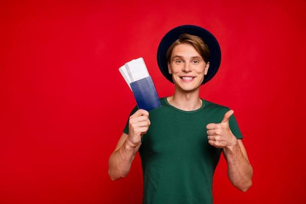 Porträt junger mann mit hut, der pass mit tickets hält