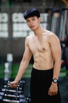 Porträt junger mann mit nacktem oberkörper, der hantel vom rack zum training im fitnessstudio nimmt,