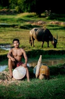 Porträt junger mann oben ohne in lendenschurz im ländlichen lebensstil sitzend mit bambus-fischerfalle