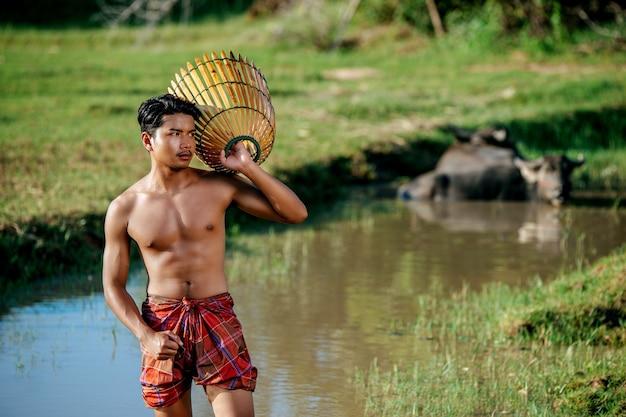 Porträt junger mann oben ohne verwenden bambus-fangfalle, um fisch zum kochen zu fangen, asiatischer junger bauernmann im ländlichen lebensstil