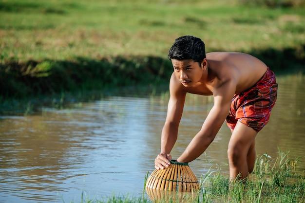 Porträt junger mann oben ohne verwenden bambus-fangfalle, um fisch zum kochen zu fangen