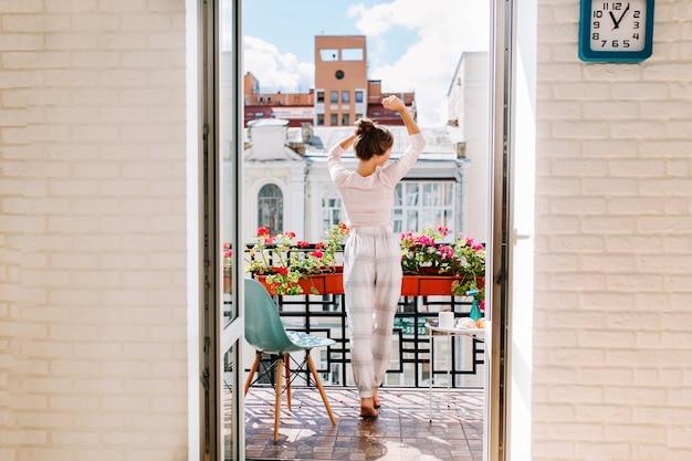 Porträt junges mädchen im pyjama, das auf balkon in der stadt am sonnigen morgen bewegt. ihre langen haare fliegen im wind, sie lächelt.