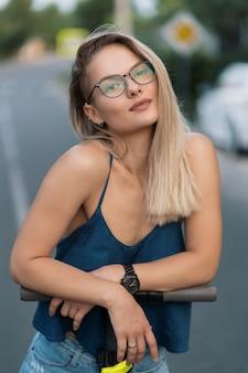 Porträt junges schönes mädchen in der brille, die einen elektroroller im sommer auf der straße reitet