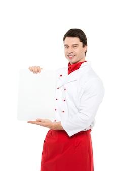 Porträt kaukasischer mann in der kochuniform hält ein typenschild für menü auf weiß.