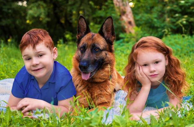 Porträt kinder und hund jungen und mädchen rothaarige im park auf dem rasen