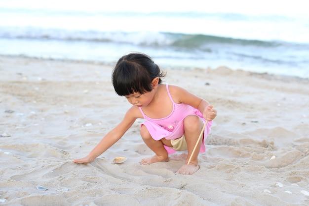 Porträt kindermädchen, das sand am strand spielt