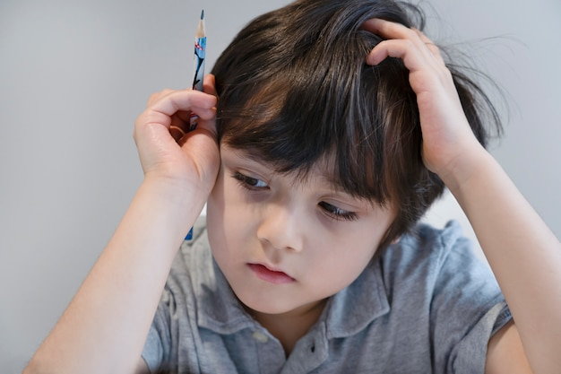 Porträt-kindjunge, der schwarzen stift hält, der allein sitzt und mit gelangweiltem gesicht nach unten schaut, einsames kind, das mit traurigem gesicht unten auf tisch schaut, fünfjähriges kind, das mit schulhausaufgaben gelangweilt ist, verwöhntes kind