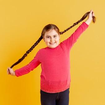 Porträt kleines mädchen, das mit ihren haaren spielt